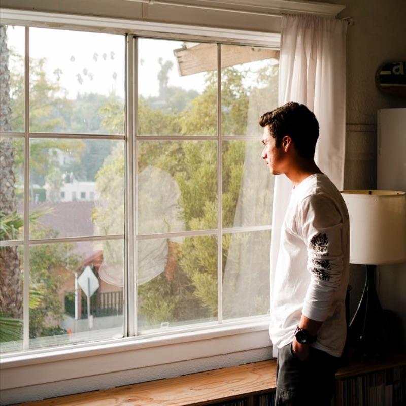 Homme qui regarde par la fenêtre